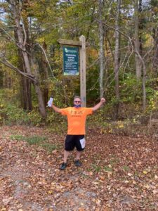 Man standing under a sign in forest